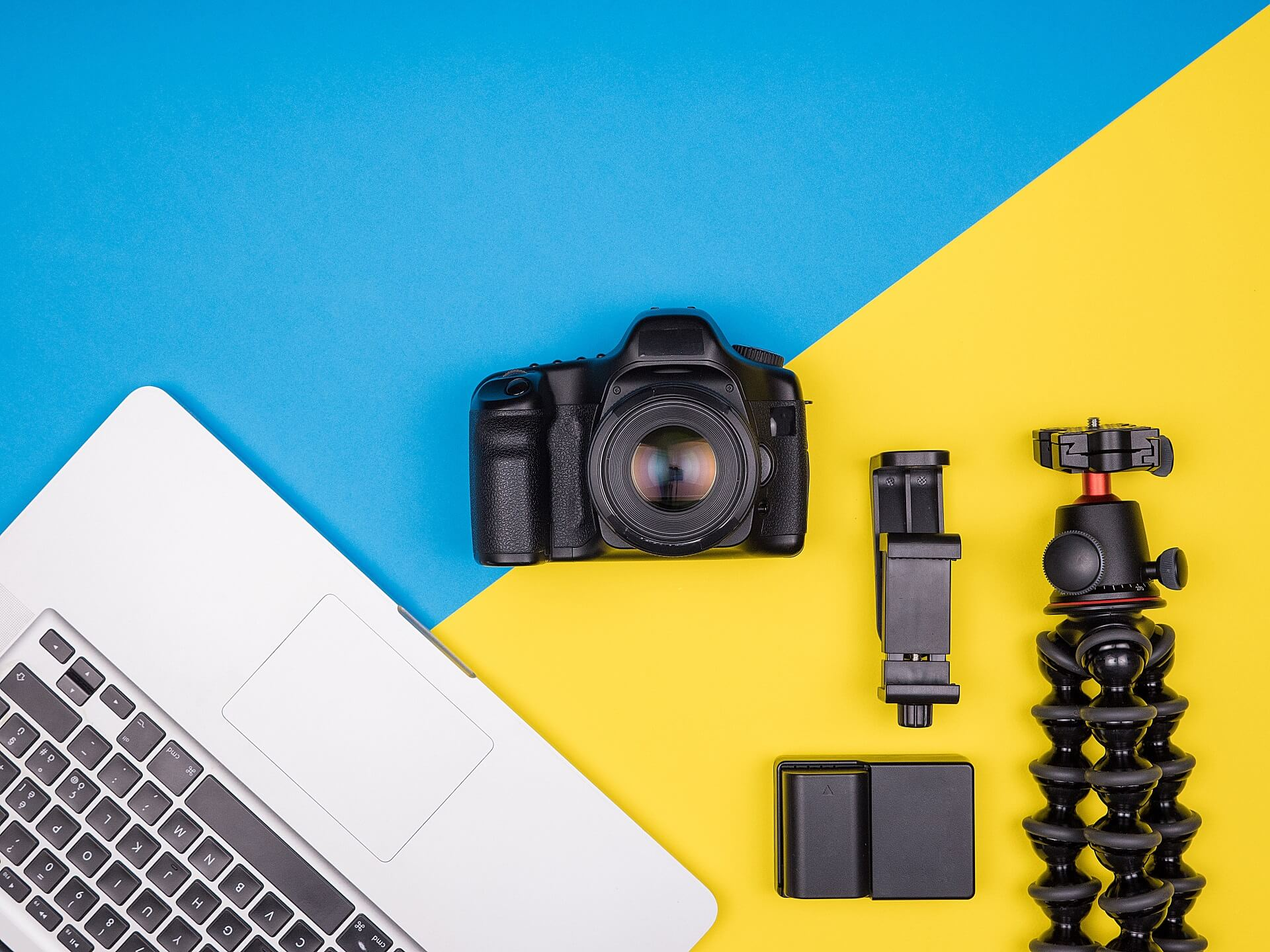Dslr camera with accessories next to a laptop