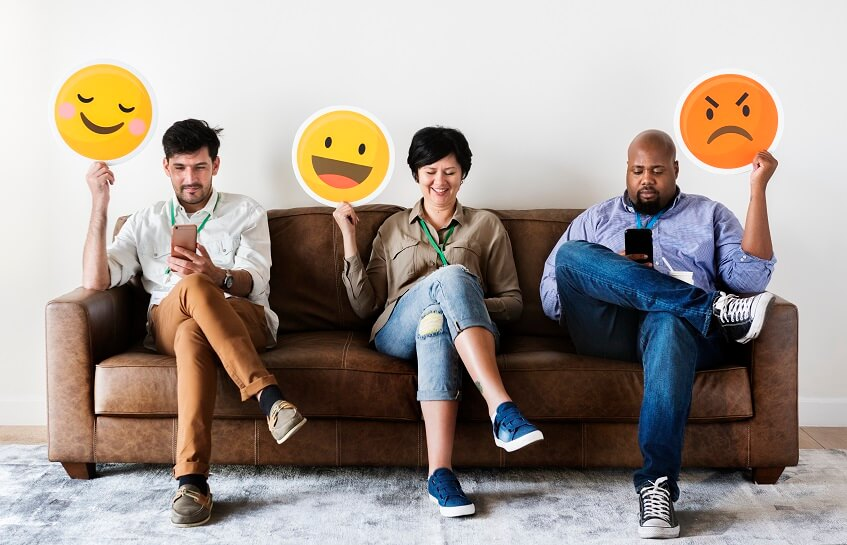 people on social media on smartphones holding different emojis to show their sentiment