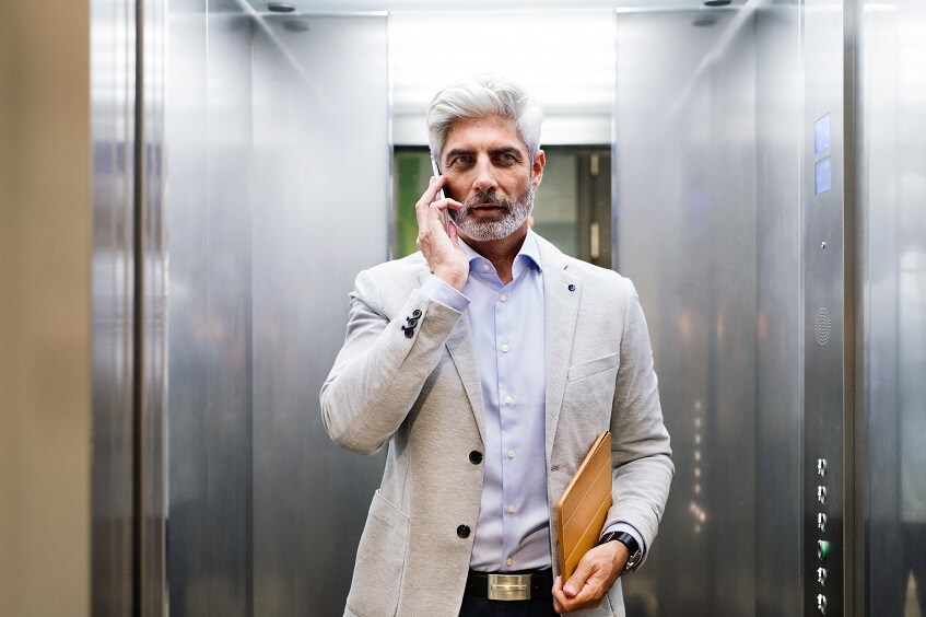 mature white collar man talking on the smartphone while in elevator