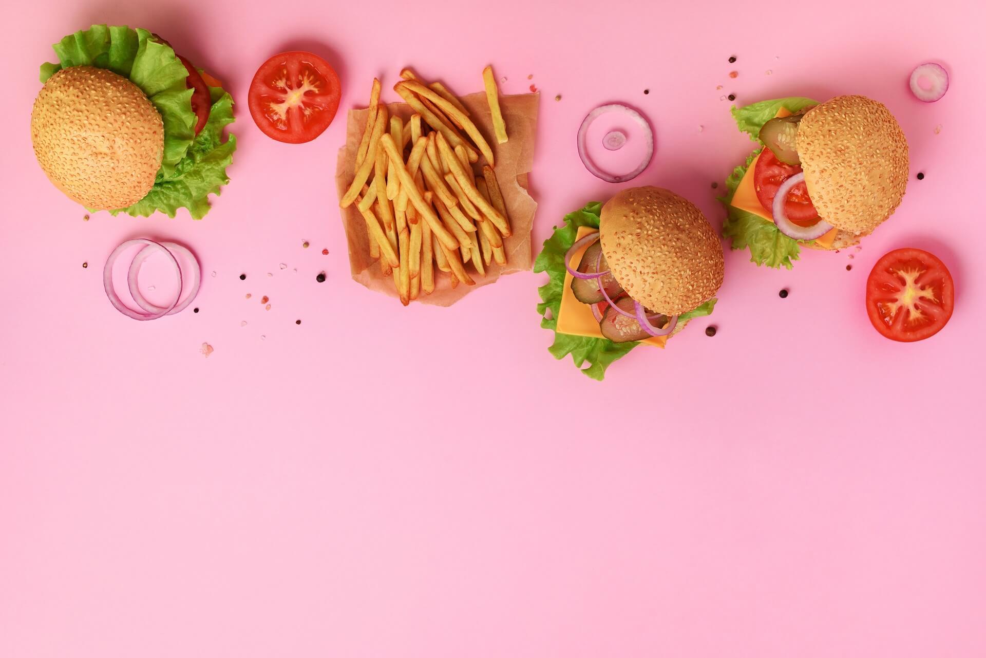 tasty burgers, fries, fresh veggies depicting fast food industry
