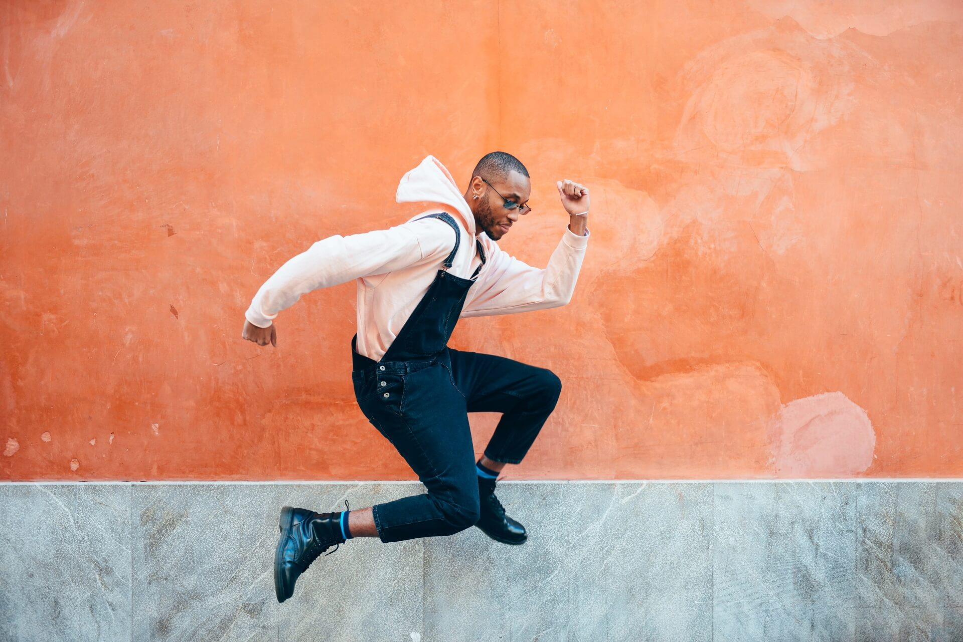 young black influencer in casual attire jumping with joy