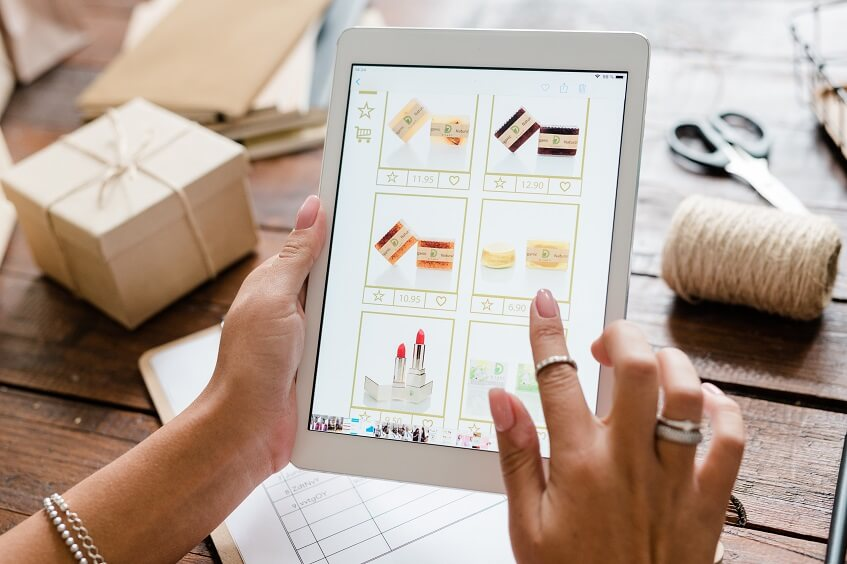 female hand choosing makeup products on a tablet from an ecommerce site