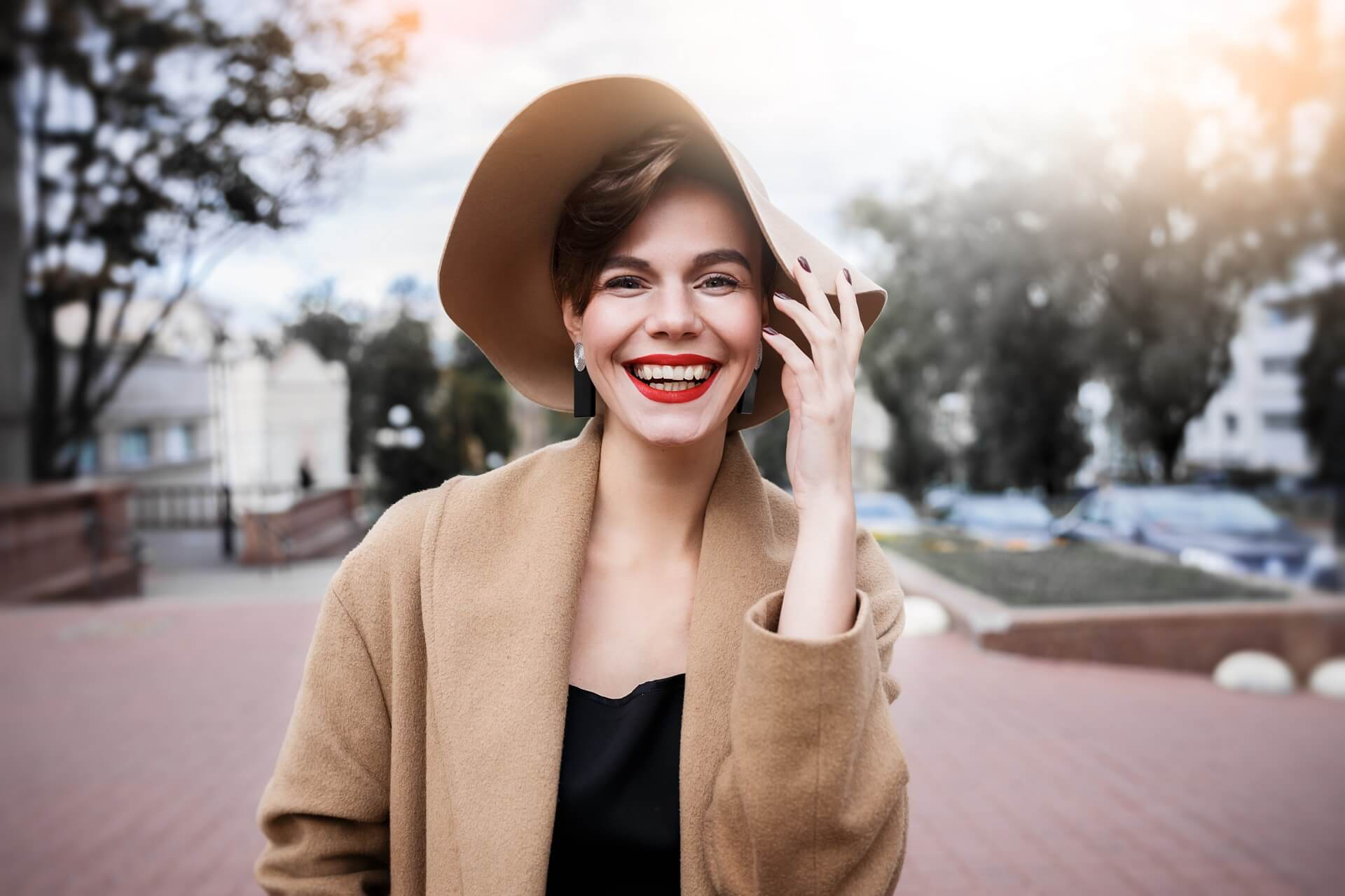 woman with heavy makeup smiling at camera outdoors